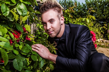 Portrait of young beautiful fashionable man against summer garden   Stock Photo - 15577380