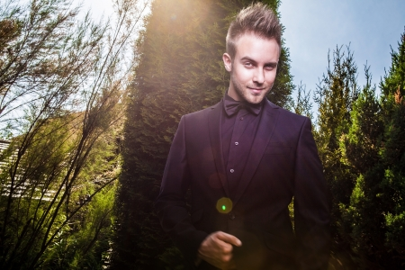 Portrait of young beautiful fashionable man against summer garden   photo