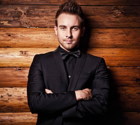 male fashion model: Portrait of young beautiful fashionable man against wooden wall