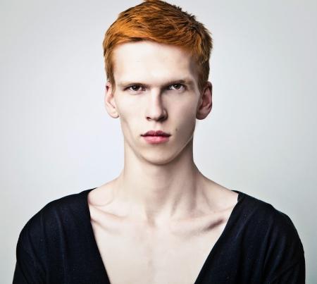 Jeune homme aux cheveux rouges sur fond clair