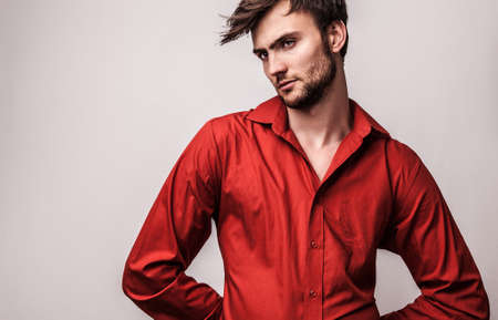 Elegant young handsome man pose on red shirt  Studio fashion portrait   photo