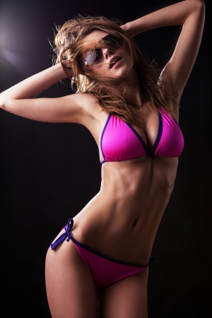 Pretty tanned woman in bikini on black background   Banque d'images