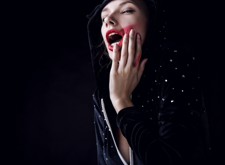 freaky: Posing woman in fashionable costume on dark background
