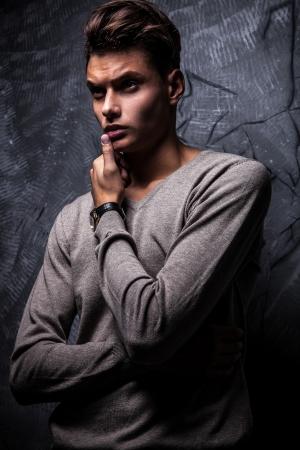 Élégant beau jeune homme sur fond grunge studio fashion portrait