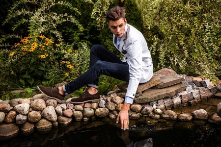 Portrait of young beautiful fashionable man against autumn garden   photo
