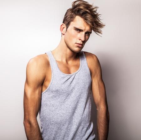 poses de modelos: Elegant Studio joven apuesto hombre de moda retrato