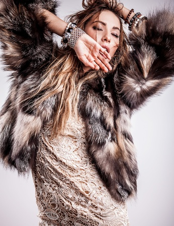Portrait of attractive stylish woman in fur against grey background Stock Photo - 17104628