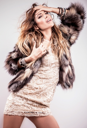 Portrait of attractive stylish woman in fur against grey background   Stock Photo - 17104626