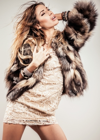 Portrait of attractive stylish woman in fur against grey background   Stock Photo - 17104505