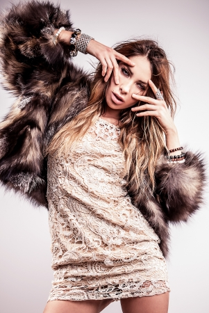 Portrait of attractive stylish woman in fur against grey background   Stock Photo - 17130116