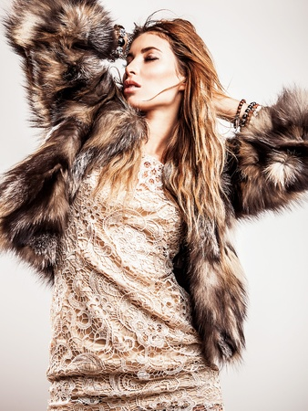 Portrait of attractive stylish woman in fur against grey background   Stock Photo - 17104578