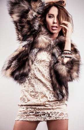 Portrait of attractive stylish woman in fur against grey background   Stock Photo - 17104577