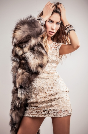 Portrait of attractive stylish woman in fur against grey background   Stock Photo - 17104631