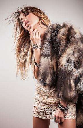 Portrait of attractive stylish woman in fur against grey background   Stock Photo - 17104635