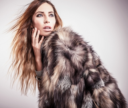 Portrait of attractive stylish woman in fur against grey background   Stock Photo - 17104643