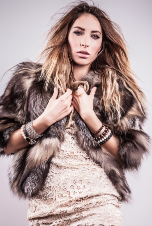 Portrait of attractive stylish woman in fur against grey background Stock Photo - 17324287