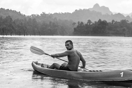 kao sok: Strong young man in kayak on the picturesque lake in Thailand