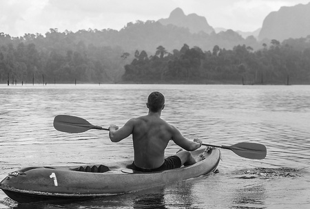 Strong young man in kayak on the picturesque lake in Thailand  photo