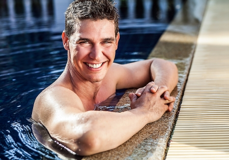 1 mature man: Adult smiling attractive man at the swimming pool  Stock Photo