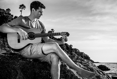 hollidays: Attractive romantic guitarist play music siting on beach rock  Stock Photo