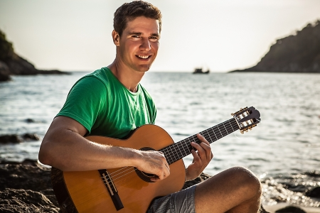 Handsome smiling guitarist play music siting on beach rock  photo