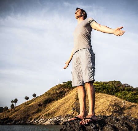 Satisfied man on stone top on evening beach  photo