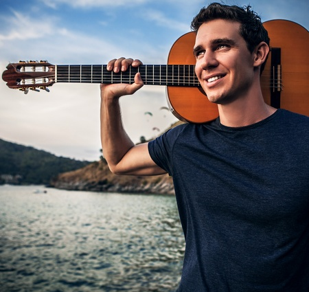 Handsome smiling man pose near evening beach with guitar  photo