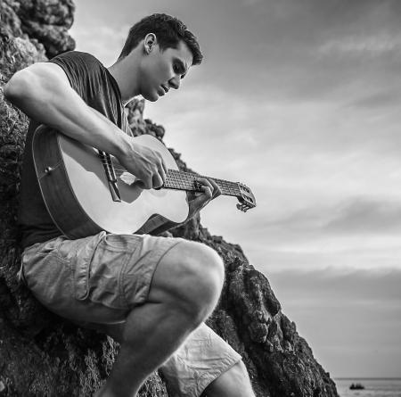 Handsome romantic man pose near evening beach with guitar  photo