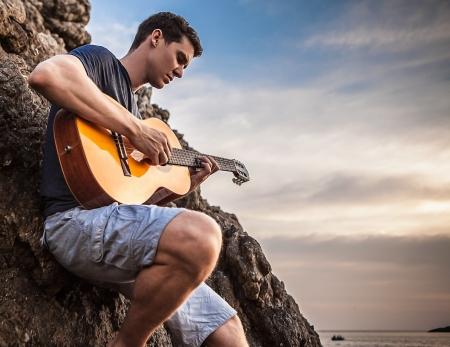 해변의 바위에 매력적인 로맨틱 한 기타리스트 놀이 음악의 부지 선정 스톡 콘텐츠