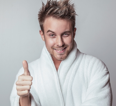 Handsome smiling young man in luxurious bathrobe    photo