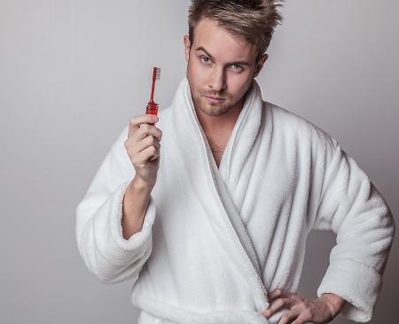 Beautiful adult man on white bathrobe brushing teeth