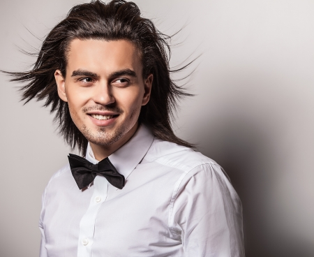 Portrait of handsome long-haired stylish man with bow tie    photo