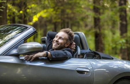 Élégant jeune homme heureux en plein air de la voiture décapotable