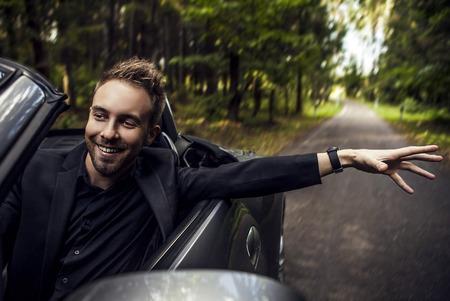 Légant jeune homme heureux en plein air de la voiture décapotable Banque d'images - 22572219