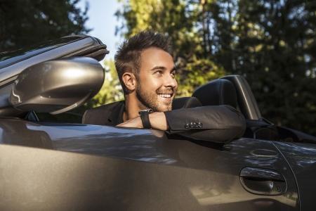 luxury car: Elegant young happy man in convertible car outdoor