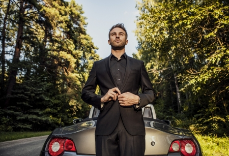 convertible car: Elegant young happy man in convertible car outdoor