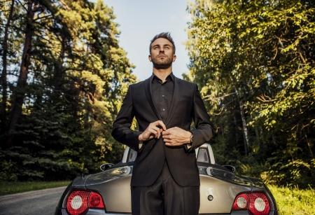 Elegante junge glücklicher Mann in Cabrio im Freien