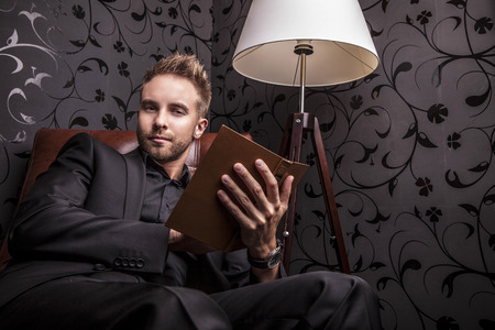Handsome young man in dark suit relaxing on luxury sofa