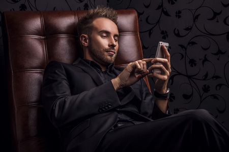 luxury lifestyle: Handsome young man in dark suit relaxing on luxury sofa