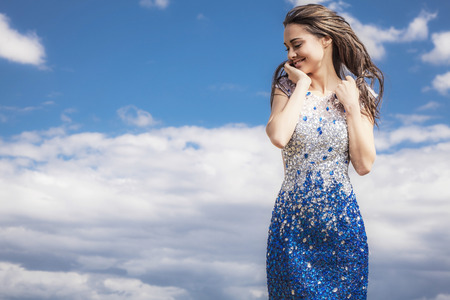 Young sensual beauty smiling woman in a fashionable dress pose outdoor