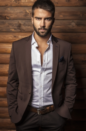 hombre: Retrato de hombre joven de moda hermosa contra la pared de madera Foto de archivo