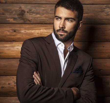 man close up: Ritratto di giovane uomo bello alla moda contro la parete di legno