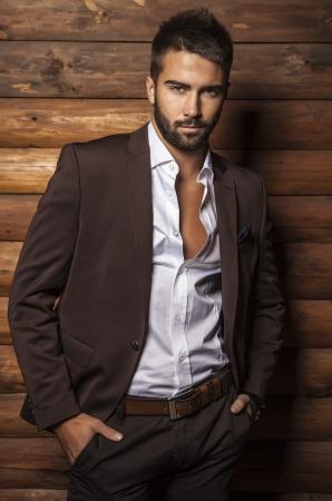hombre con barba: Retrato de joven bella hombre de moda contra la pared de madera Foto de archivo