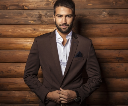 Portrait of young beautiful fashionable man against wooden wall 版權商用圖片 - 22572460