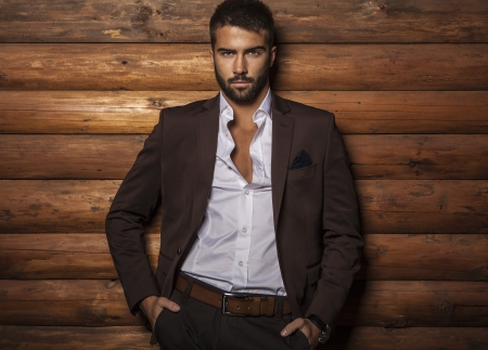 Portrait of young beautiful fashionable man against wooden wall
