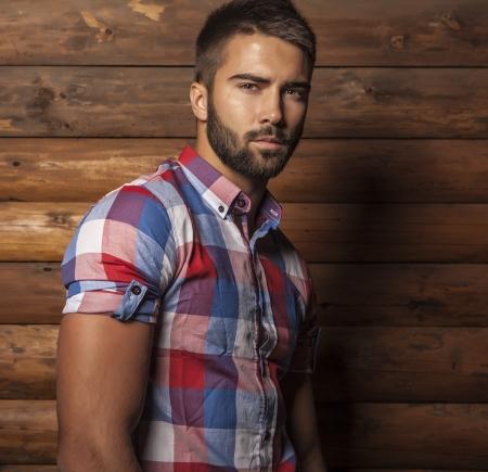 Portrait de jeune homme ? la mode belle contre le mur en bois