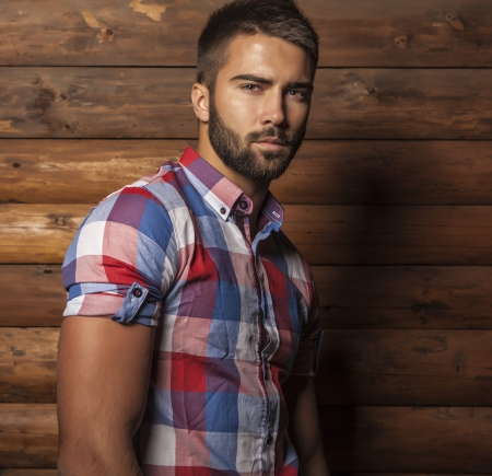 Portrait of young beautiful fashionable man against wooden wall 版權商用圖片 - 22572465