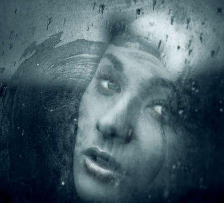 Art portrait of a beautiful young spooky woman, looks through grunge styled rainy window    photo