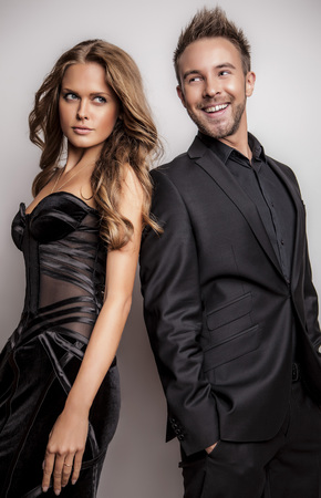 Portrait of young attractive couple posing at studio dressed in black fashionable clothes    photo