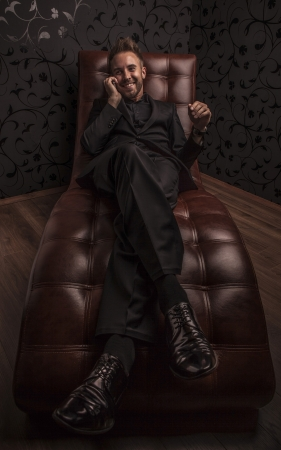 Handsome young business man in dark suit relaxing on luxury sofa    photo